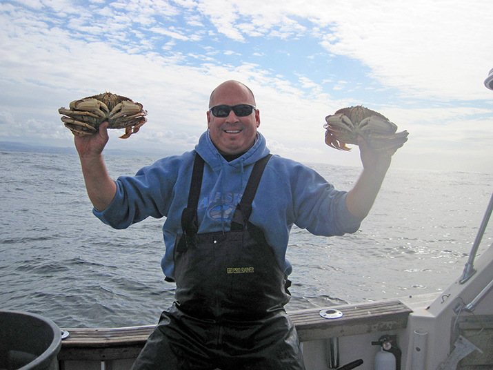 Man on a boat holding two crabs