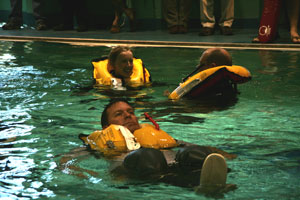 3 people testing life vests in the pool at a safety-at-sea seminar