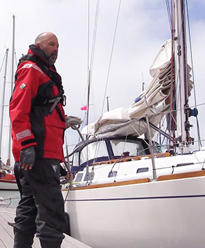 Sailor in foul weather gear with Sailboat