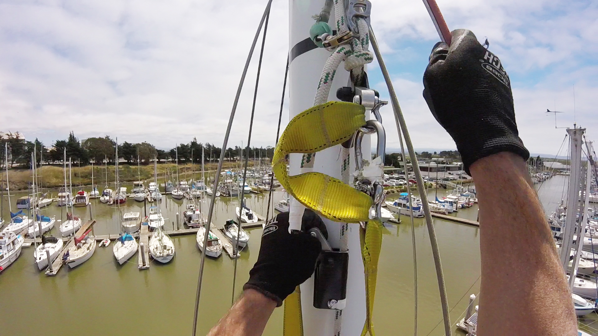 When you get to the top of the mast, you can connect a carabiner that's  part of the harness to the upper jammer to raise yourself to masthead level.