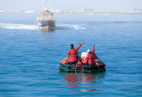 boaters on a liferaft signaling for help