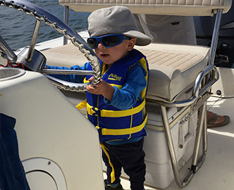 Little boy at helm of boat