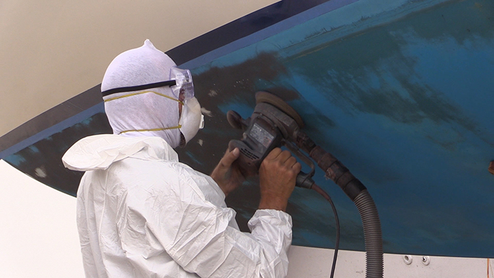 person using a electric sander with a vacuum system to remove the bottom paint on a boat