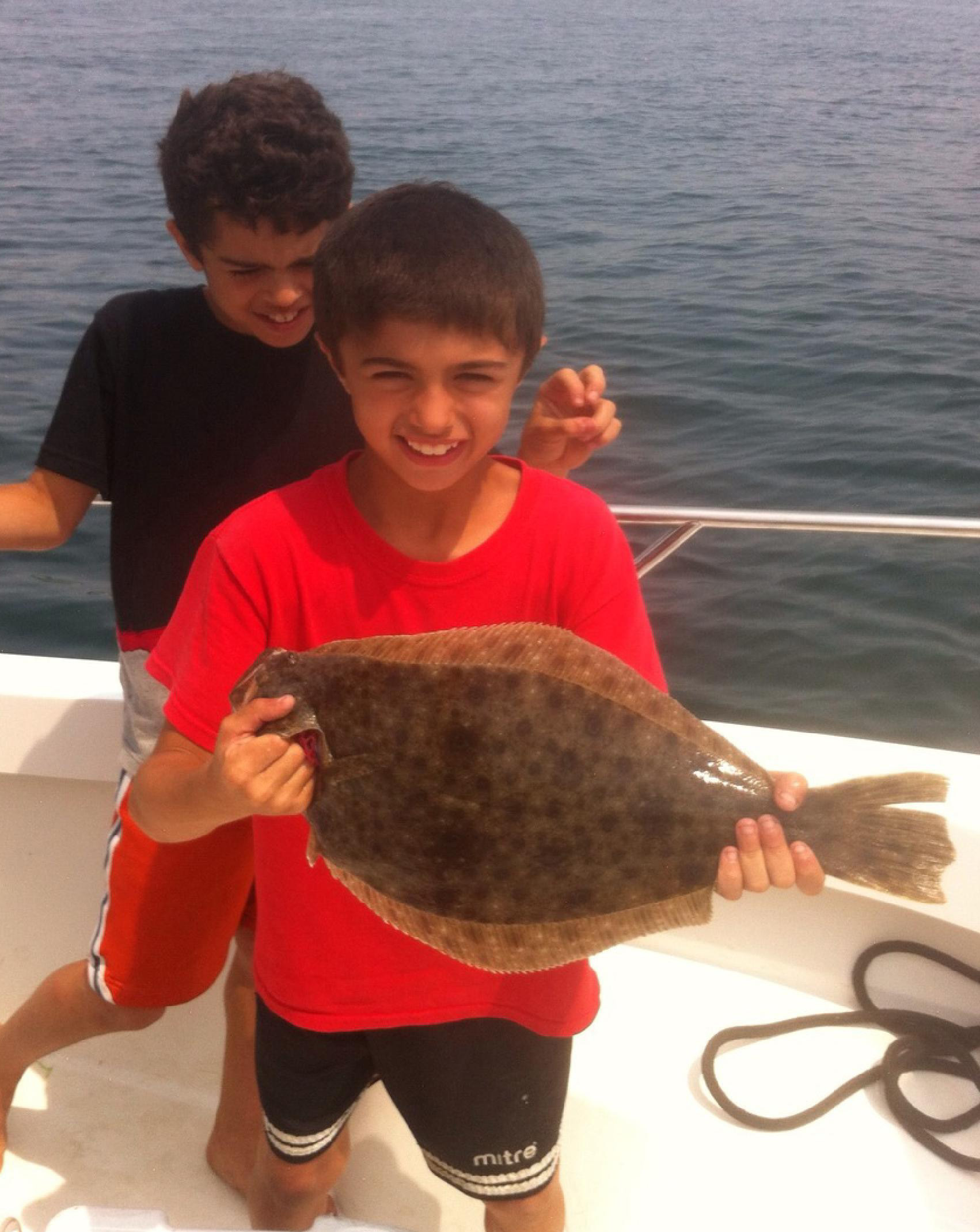 Boy holding up fluke with brother behind him